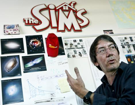 Will Wright next to the logo of his game franchise The Sims.